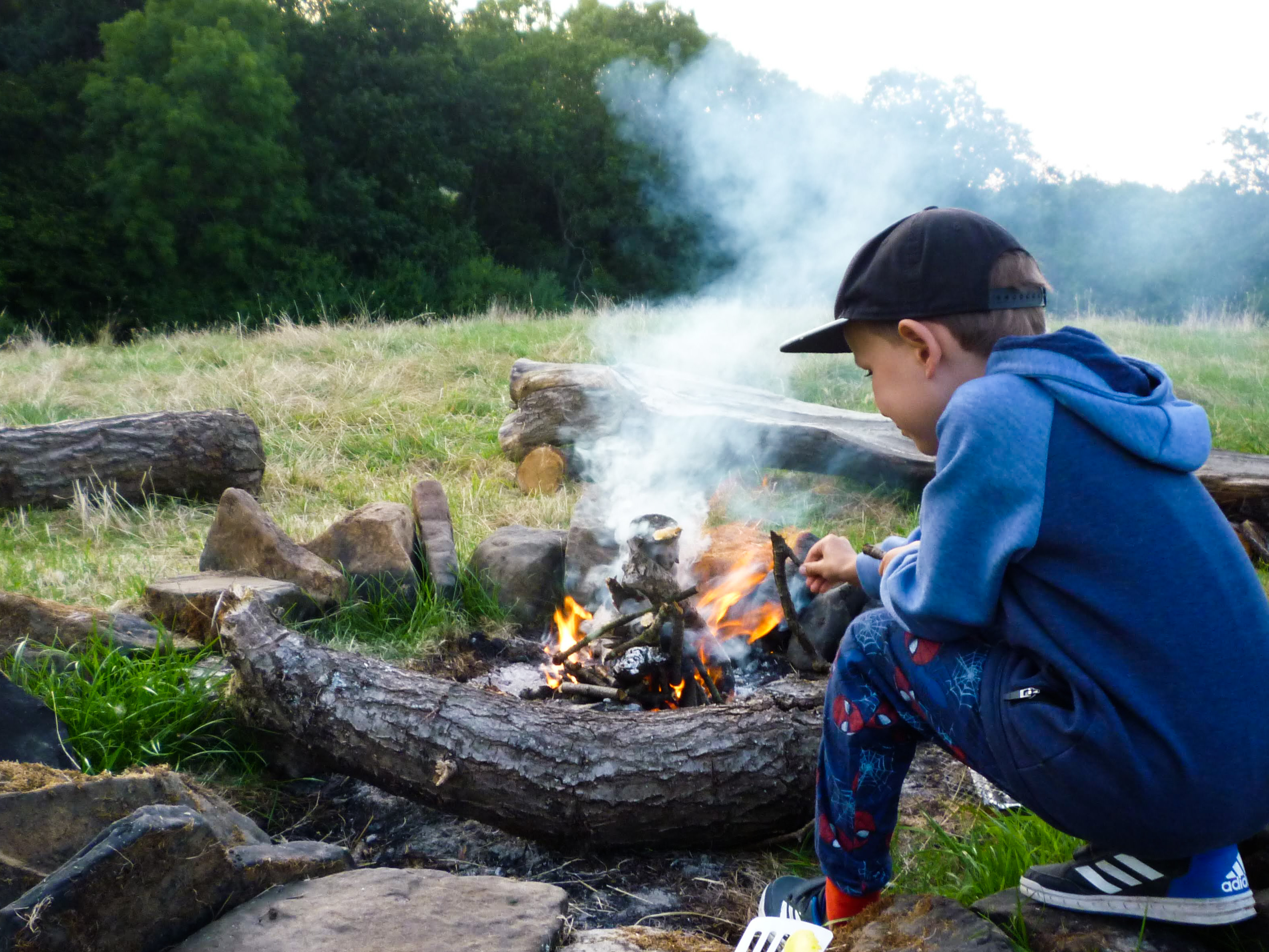 Little boy helping to build a fire