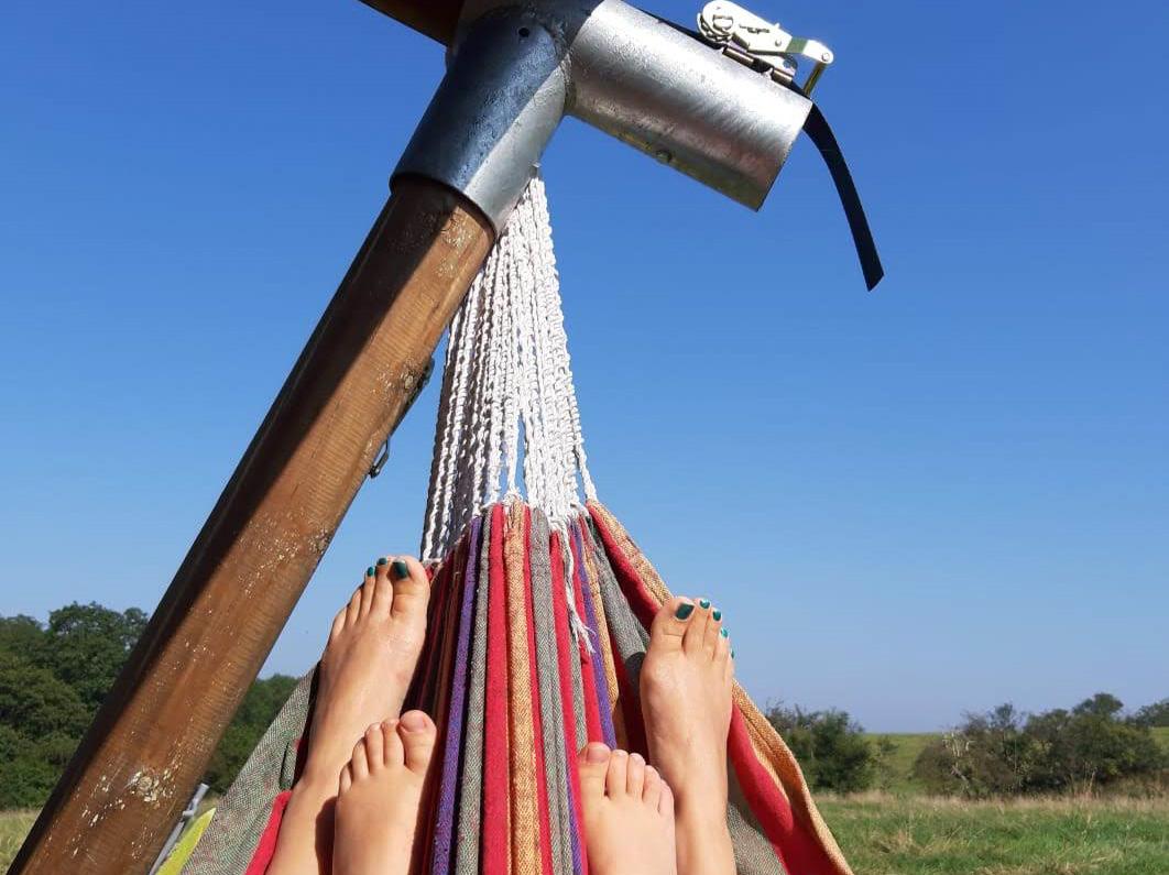 Feet in a hammock with a big blue sky