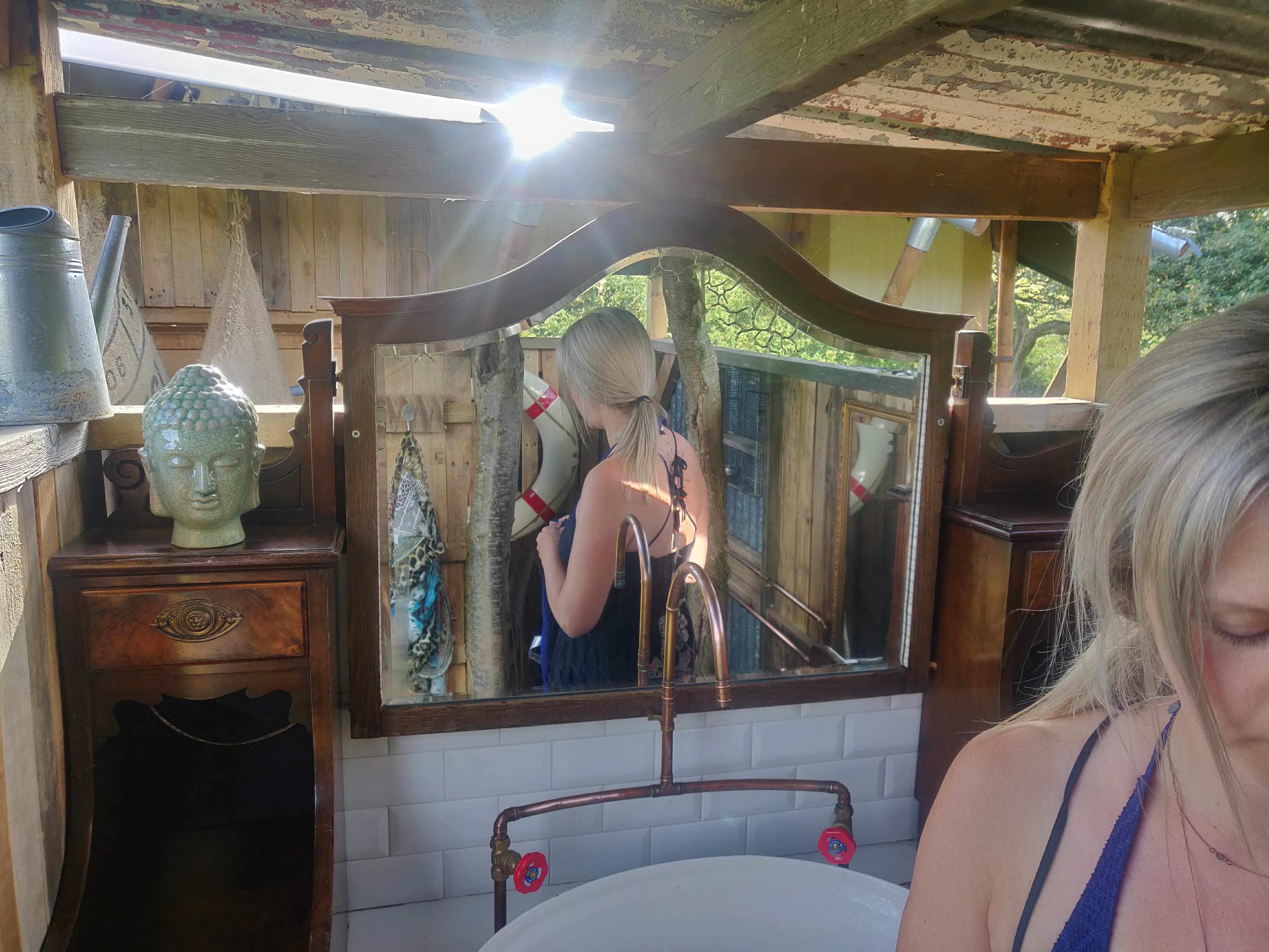 Girl taking a shower in our beautiful glamping bathroom